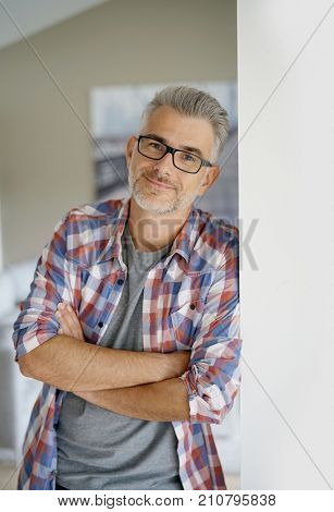 Smiling 40-year-old man standing at home