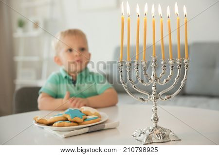 Cute boy sitting at table with nine-branched menorah and festive cookies