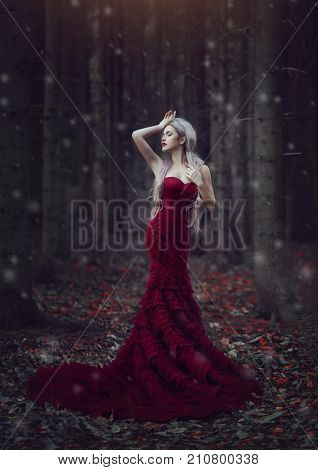 Beautiful elegant woman with long white hair posing in a luxurious red dress with a long train standing in a autumn pine magical forest and snowing. Creative colors and Artistic processing.