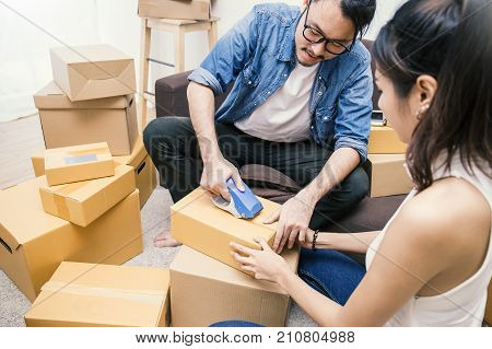 Young asian man and woman taping up a cardboard box in the office SME business relocation and new small business concept SME concept