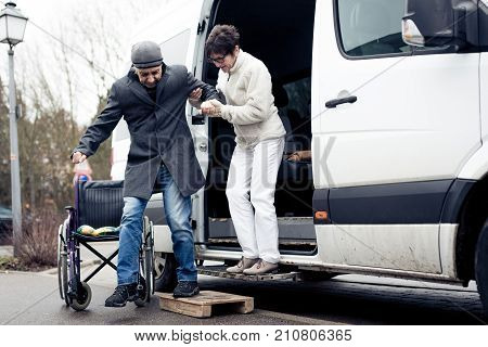nurse helping senior man exit a van and get to his wheelchair
