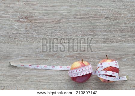 Red apple and measuring tape.The concept of weight control Lose Weight With Fruit Diet concept Adverse effects of excessive weight loss.