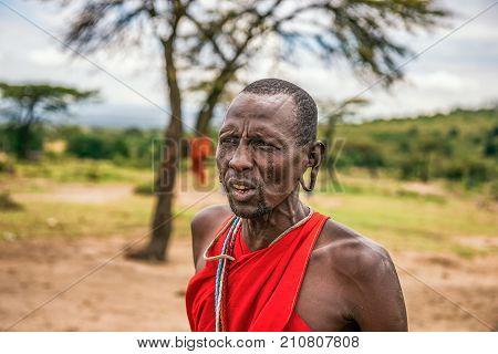 MAASAI MARA, KENYA - OCTOBER 17, 2014 : Portrait of an african men posing in his Masai tribe village. The Maasai are a Nilotic ethnic group living in southern Kenya and northern Tanzania