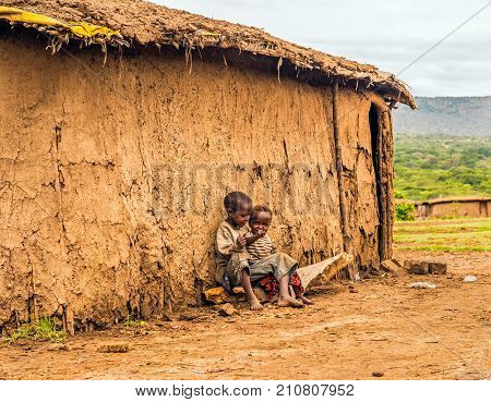 MAASAI MARA, KENYA - OCTOBER 17, 2014 : Two african boys sitting in front of a Masai tribe village house.