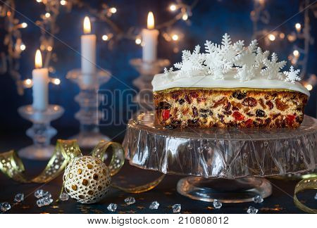 Christmas fruit cake with icing and sugar snowflakes on the glass cake stand.