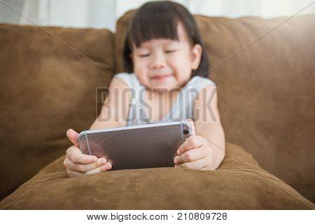 Casual asian toddler girl sitting on a couch at home playing and touching a mobile phone (smartphone) closeup Education concept