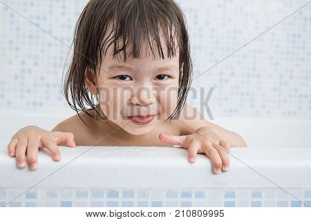 happy funny asian baby laughing and bathed in the bath little asian toddler playing hide and seek in the bath tub