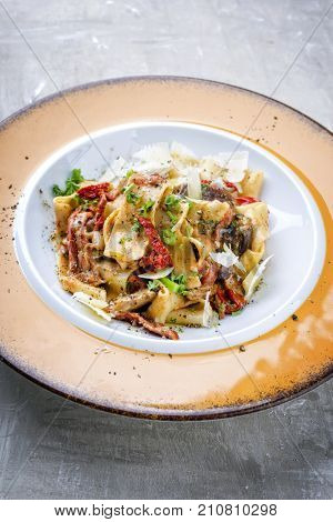 Traditional Italian pappardelle di pomodoro with mushrooms and parmesan as close-up on a plate