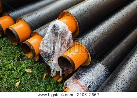 Water pipes with insulation lie on the grass. To draw water. A water pipe on a green background. Water supply in the big city. Pipes for conducting water. Drops of water on the pipe