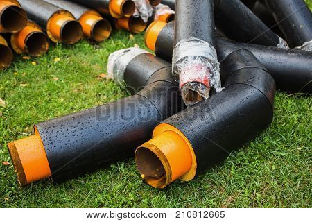 Water pipes with insulation lie on the grass. Pipes with drops of water. Pipes lie on the grass. New pipes. Pipes for water. Insulated pipes