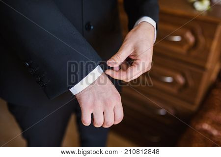 A stylish business man in a dark suit. The business man in a respectable suit button up his buttons. Business concept with suit. Business meeting. Business offer. Conceptual picture of a business man in suit