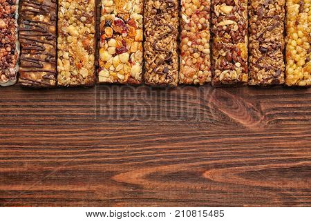 Healthy cereal bars with chocolate on wooden background