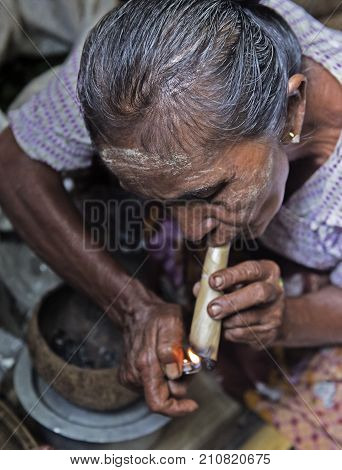 BAGAN MYANMAR- SEP 04 : Woman smoking a cheroot cigar in market in bagan Myanmar on September 04 2017. Cheroot is a cigar made by dried fruits and little bit of tobacco