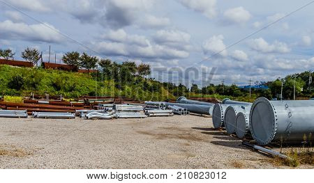 Industrial pipe storage lot with various sizes and types of pipes under a sky filled with white puffy clouds