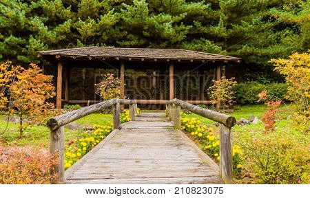 Wooden walkway with wooden post railings leading to a covered rest area in a countryside park