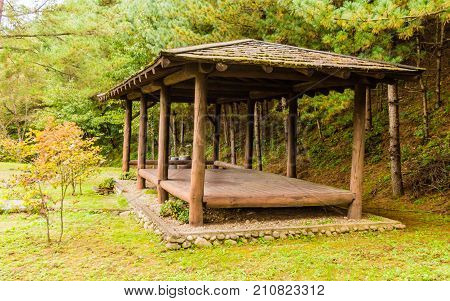 Covered rest area in a countryside park shaded by evergreen trees