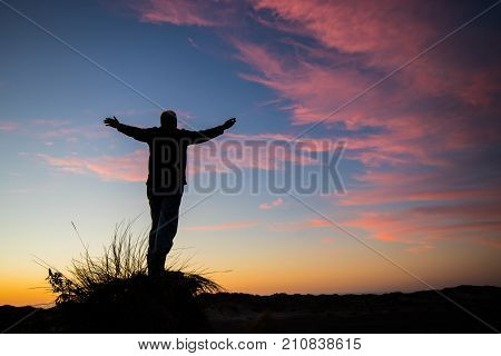Man on a hill worshiping the one and only God who created sunset.
