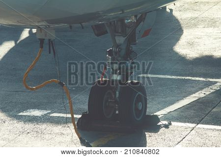 landing gear of airplane in airport, preparing for take-off, telephoto shot