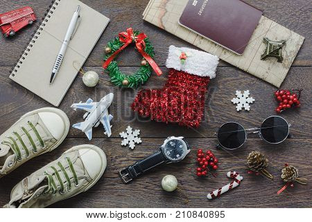 Overhead view of accessory Merry Christmas with items to travel background concept.Mix several object on the modern rustic brown wooden at home office desk.Equipment for traveler or teenage and adult.
