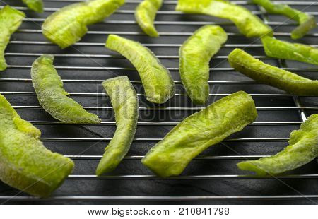 Pieces of green pomelo on the grate for drying side view horizontal