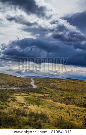 Terrible black clouds over the Chilean Patagonia. Dirt road in the National Park Torres del Paine, Chile. The concept of active and extreme tourism