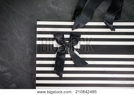 Paper bag in strip with black bow top view horizontal