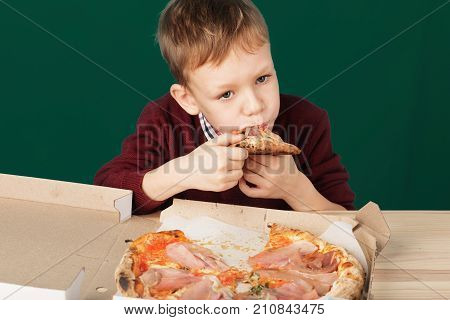Children Eat Italian Pizza In The Cafe. School Boy Is Eating Pizza For Lunch. Child Unhealthy Meal C