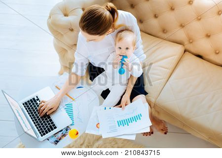Tasty toy. Tired busy hardworking businesswoman not noticing her baby putting a toy into a mouth while sitting on her knees
