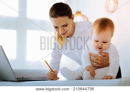 Pretty help. Enthusiastic baby trying to help a cheerful skilled engineer while sitting on the table