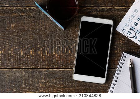 Payment card, phone, notebook and calendar on wooden boards copy space horizontal