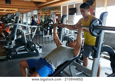Fitness trainer controlling young man who is doing bench press