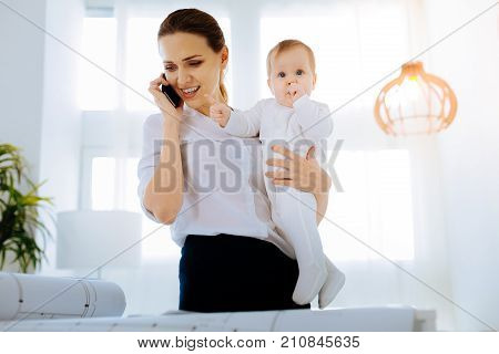 Important information. Positive kind young mother with a cute baby in her arms analyzing an important information connected with her project