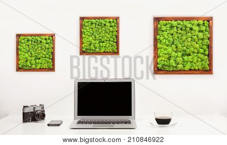 Minimalistic workplace with notebook camera mobile and cup of coffee. White background. Stylish modern sparse interior working place.