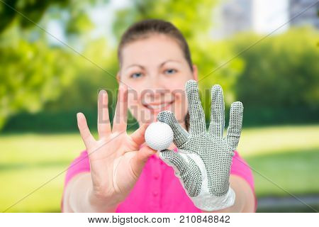 Young Girl Shows The Ball For The Game Of Golf On A Background Of Golf Courses