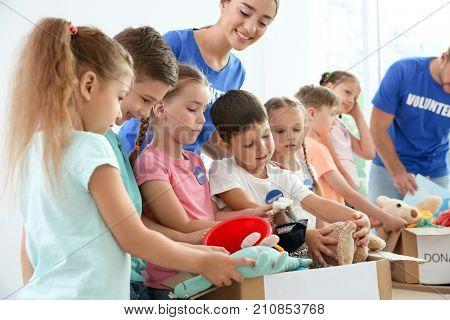 Happy volunteers with children sorting donation goods indoors