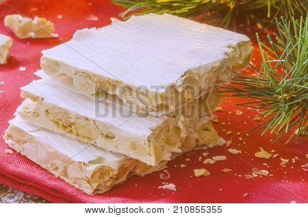 Close up of Turron typical Christmas sweet in Spain. Almond nougat on red napkin on dark wooden background with Christmas decoration snow and fir tree.