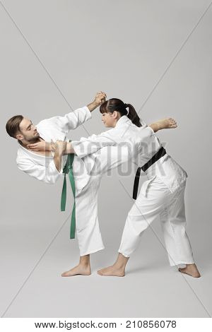 Young man and woman practicing karate on light background