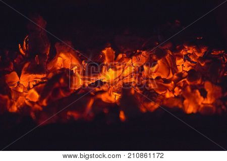 Red hot embers of burning wood inside a fireplace.
