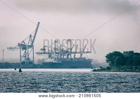 SHIP IN A SEA PORT - Transshipment terminal in the mist