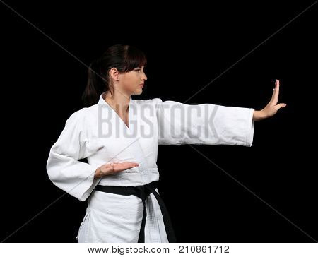 Young woman practicing karate on dark background
