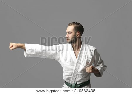 Young man practicing karate on light background