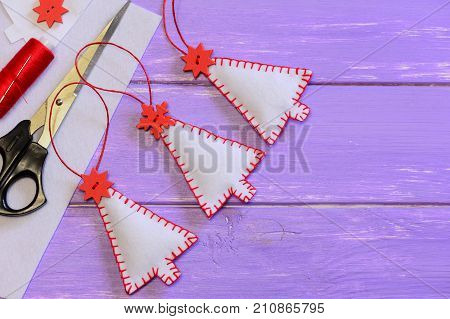 Christmas tree decorations, craft materials and tools on a wooden background with copy space for text. Easy handmade felt crafts for kids. Christmas sewing projects for holidays. Top view