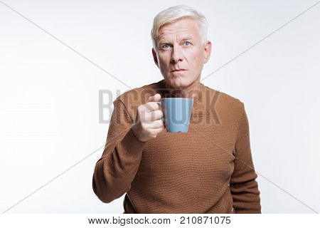 Bad coffee. White-haired senior man holding a blue cup of coffee and frowning, being unsatisfied by the poor taste of coffee