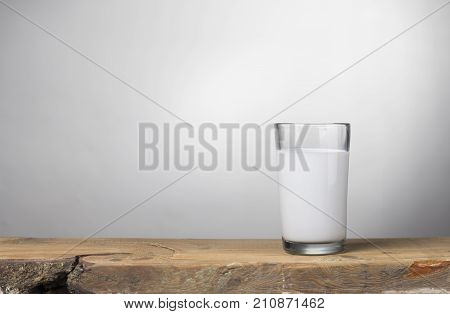 A bottle of milk and glass of milk on a wooden table on a blue background.