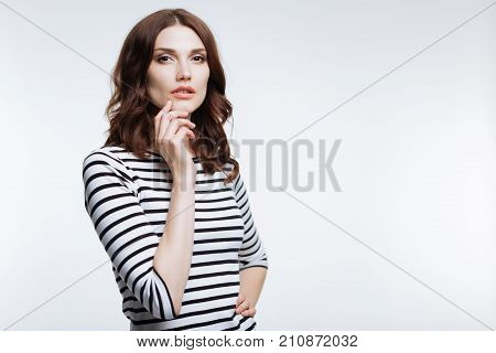 Charming pose. Gorgeous young woman with an auburn hair holding her hand on a waist and touching her chin with the other hand while standing against a white background