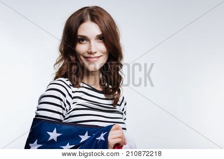 Happy American. Cheerful auburn-haired young woman in a striped pullover smiling at the camera while being wrapped in an American flag