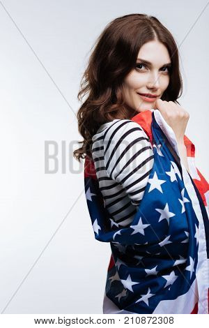 Love my nation. Pretty auburn-haired young woman posing for the camera while standing half-turned and wrapped into an American flag