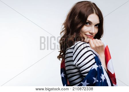 Proud of my country. Charming auburn-haired young woman being wrapped up in American flag while posing, standing half-turned against a white background