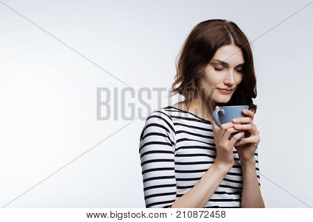 Delicious smell. Beautiful young woman smelling the scent of a coffee in a blue cup while standing against a white background