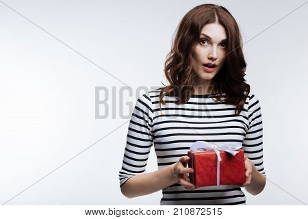Unexpected surprise. Gorgeous auburn-haired young woman holding a box with a present and looking surprised to receive it